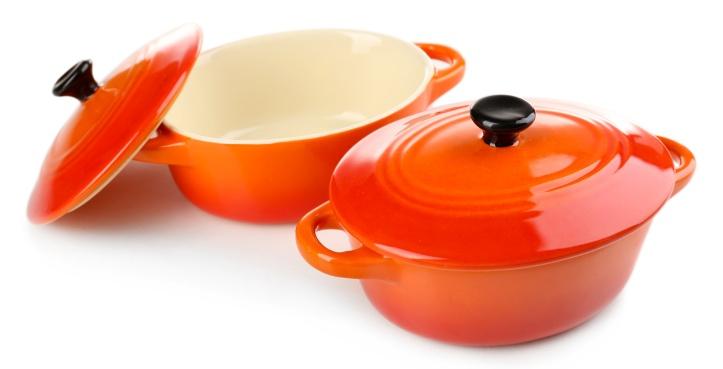 orange ceramic cookware over a white background