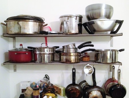 different cookware over a white background many pots and pans