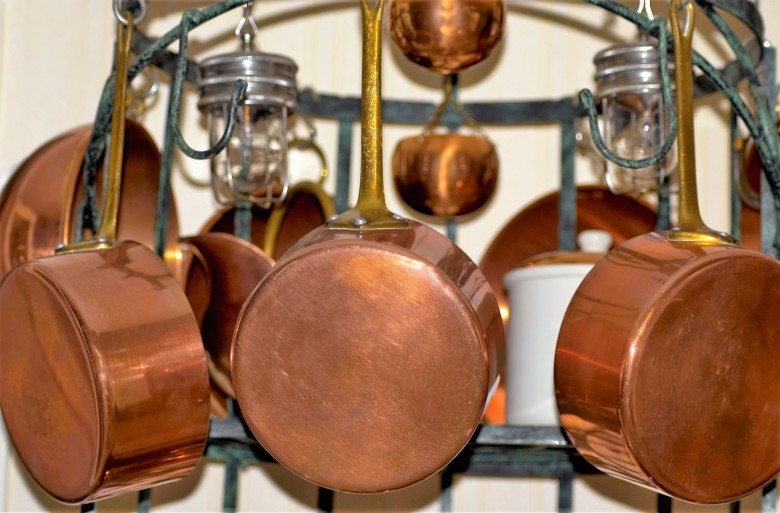 copper cookware with golden handle over white background