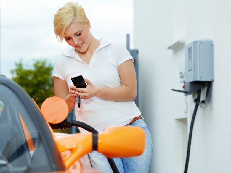 woman with mobile phone charging orange electric car at home