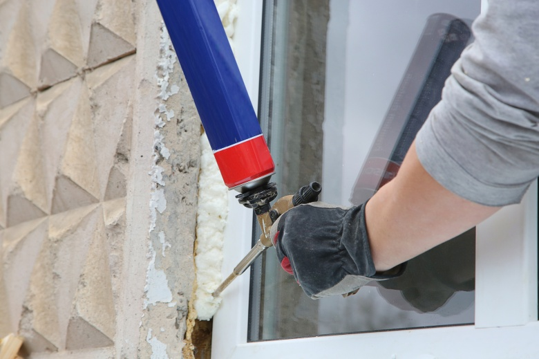 Worker's hand fix a window by  polyurethane foam