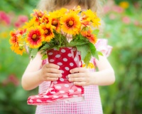 girl holds beautiful flowers in red welly boots against spring background