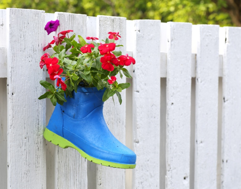 blue welly boot hanging on a wood gate wall with flowers inside