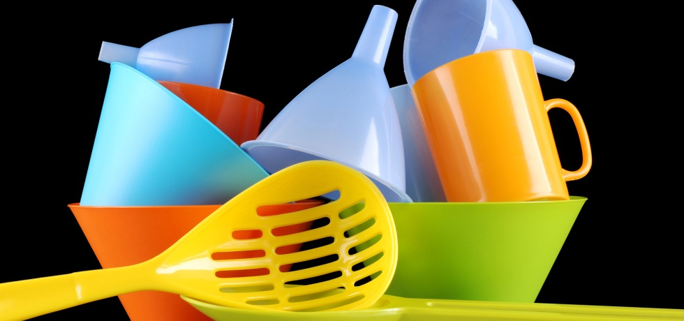 colored kitchenware on a black background, different color of kitchen utensils
