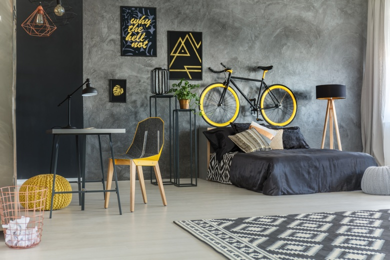 Grey student room with bed, desk, bike and copper lamps