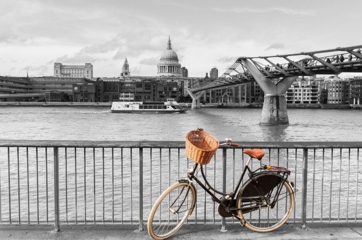 Bicycle with wicker basket standing out in color against the black and white backdrop of the River Thames, St Paul's cathedral and the Millennium Footbridge (aka Wobbly Bridge), London, England, UK