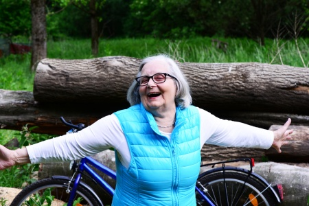 Old woman cycling smiling, healthy and happy in a green park