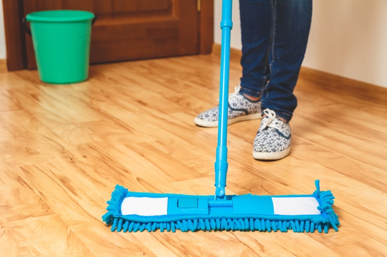 Young woman washing wooden floor with blue microfiber mop and green bucket