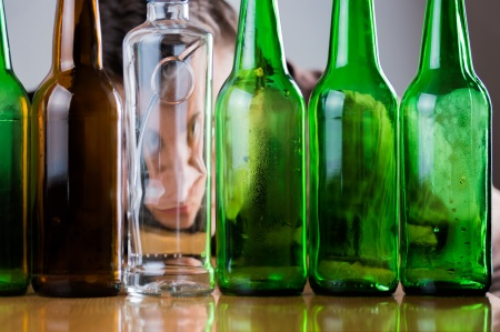 young man behind green, clear and brown glass bottles.