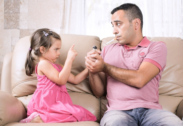 man smokes indoors while little girl disaproves her smoking father