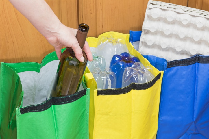 Female hand is sorting empty wine bottle to the green bag and plastic bottles to yellow bag