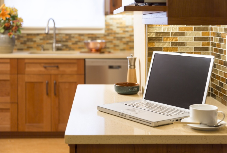 Laptop computer in contemporary upscale home kitchen interior with cherry wood cabinets, quartz countertops and glass tile mosaic backsplash