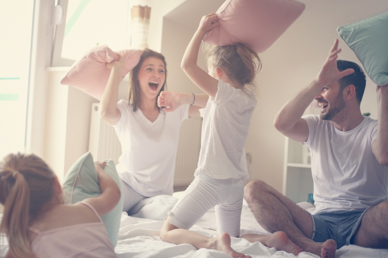 Happy family having fun on bed.
