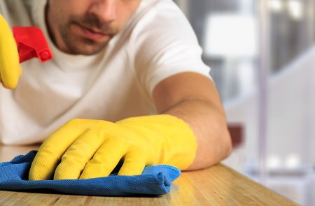 man cleaning wooden surface with yellow gloves and spray