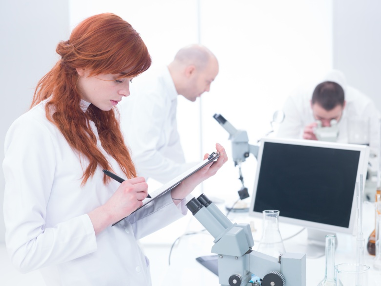 people working in chemistry lab, female scientist in the front taking notes, 2 males analyzing under microscope in the background around a lab table