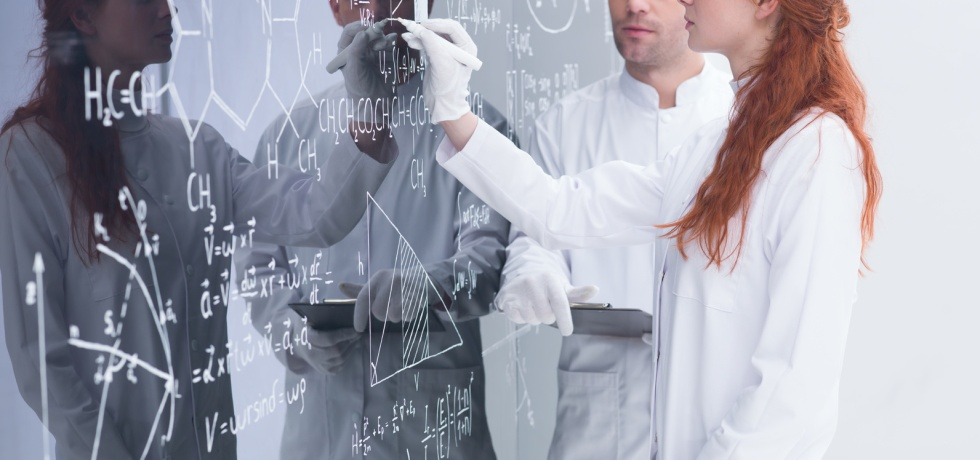 side-view of a female scientist in white robe and gloves in a chemistry lab writing on a blackboard formulas and male observe