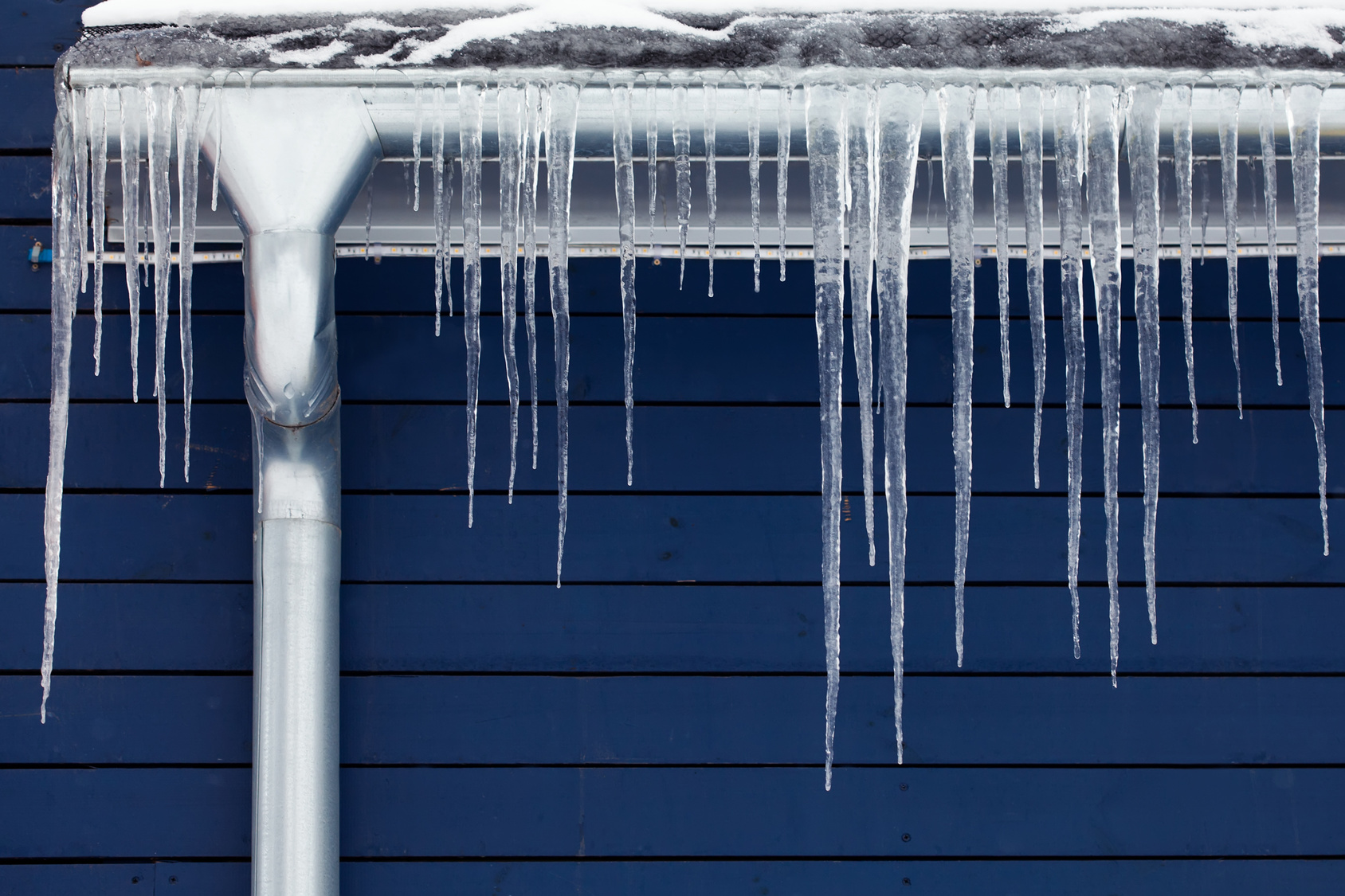 Icicles on the roof. Winter concept. downspout. Blue wooden background.
