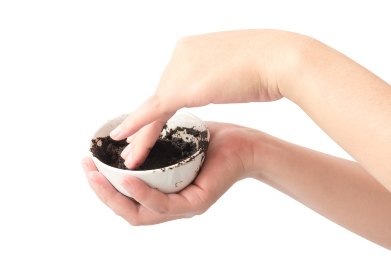 Woman's hand holding bowl of coffee grounds for skin scrub, health care and beauty concept