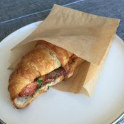 Lobster Croissant in eco takeaway paper bag form if you care brand on a plate