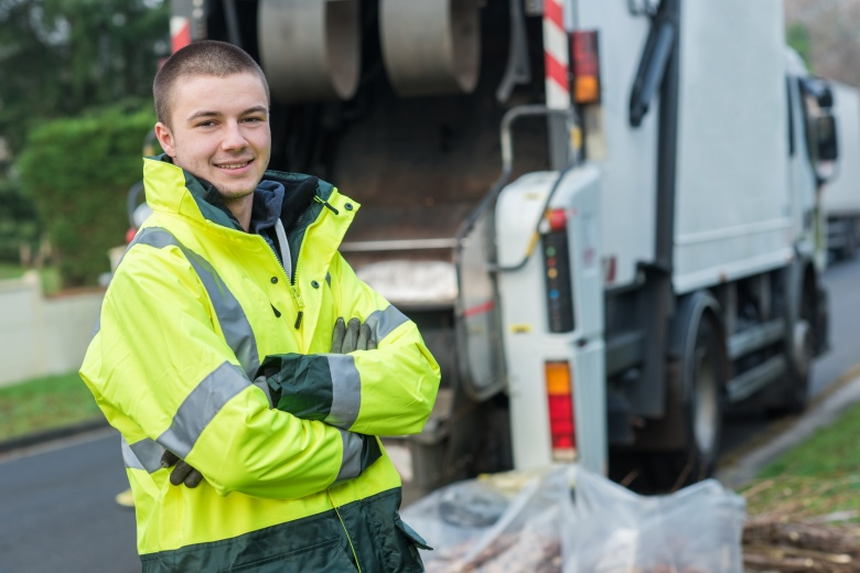young smiling waste collector near truck on the background